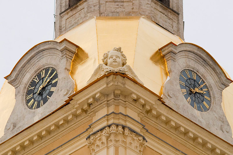 A clock and an image of a cherub at the Peter and Paul Cathedral in Saint-Petersburg, Russia