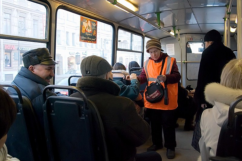 A conductor collects fares on a St. Petersburg bus